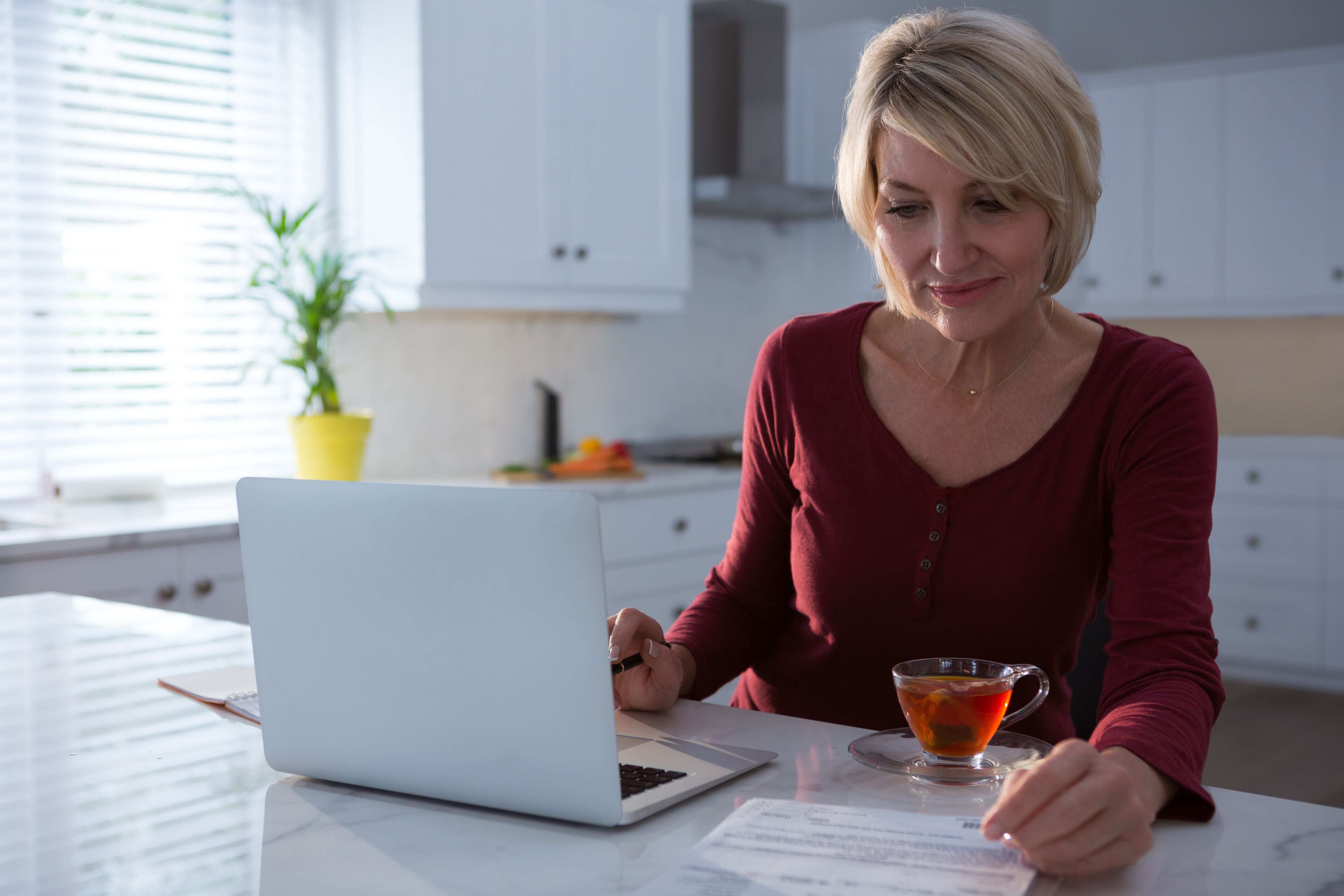 person working remotely from home in kitchen with laptop